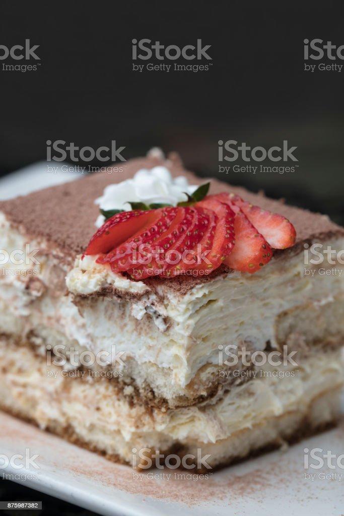 Italian Tiramisu made with chocolate and layers of cake and cream, topped with strawberries stock photo