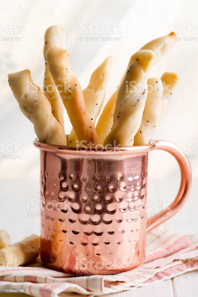 El pan casero tradicional italiano pega grissini en una taza de cobre sobre una mesa de madera. - Foto de stock de Abdominales libre de derechos