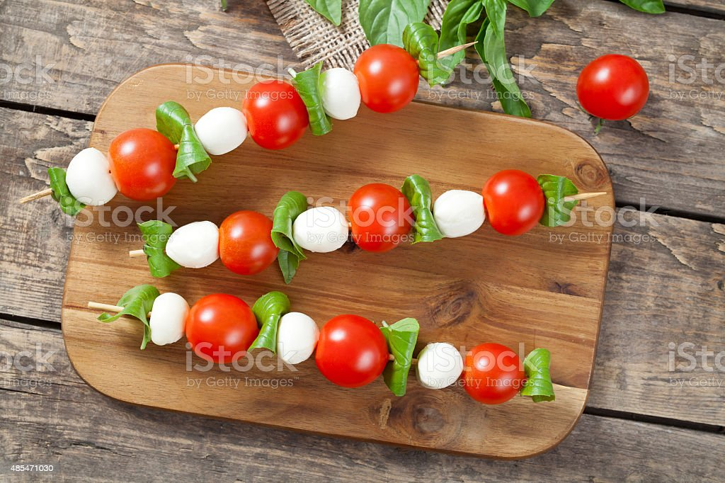 Italian traditional homemade skewers with mozzarella tomatoes and basil called stock photo