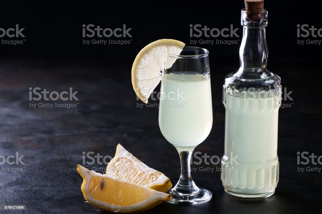 Italian traditional liqueur with lemons on the vintage table, selective focus stock photo