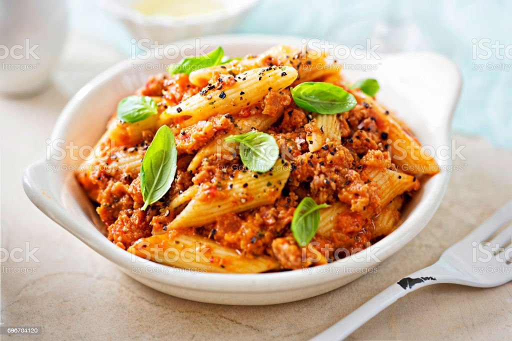 Italian tuscan sausage penne in tomato sauce with basil stock photo