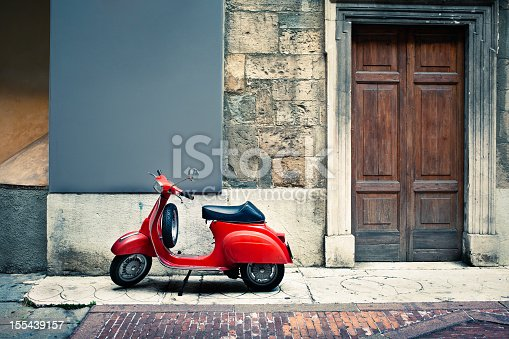 A vintage red Italian scooter stands on a sidewalk beside an old-fashioned wooden door.  The wall and sidewalk are clearly old and are patched with various materials including stone and brick.  The scooter is clean and shiny looking, with a glossy black seat.
