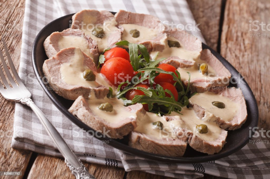 Italian Vitello tonnato with tuna sauce and capers close-up. horizontal stock photo