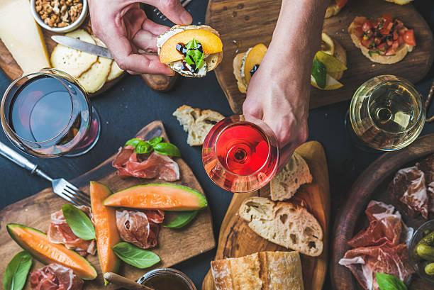 Italian wine snack variety, man's hands holding glass of stock photo