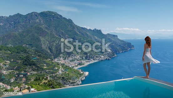 Italy. Amalfi Coast. A young woman standing on the edge of  an infinity pool of a private luxury villa of Ravello watching the coastline .