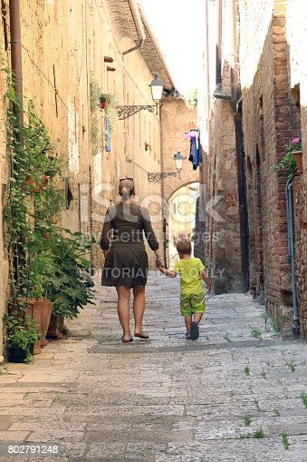 istock 06/03/2017., Italy, Colle di val d'elsa; Mother and son are having a walk throught medieval italian city 802791248