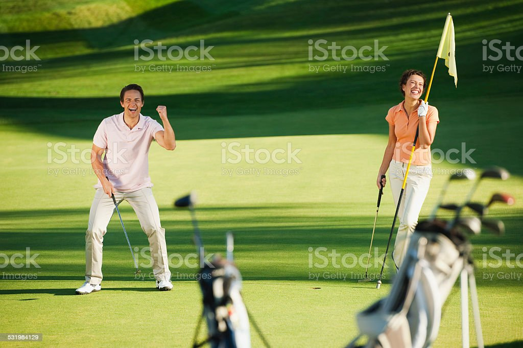 Italy, Kastelruth, Golfers playing golf on golf course stock photo