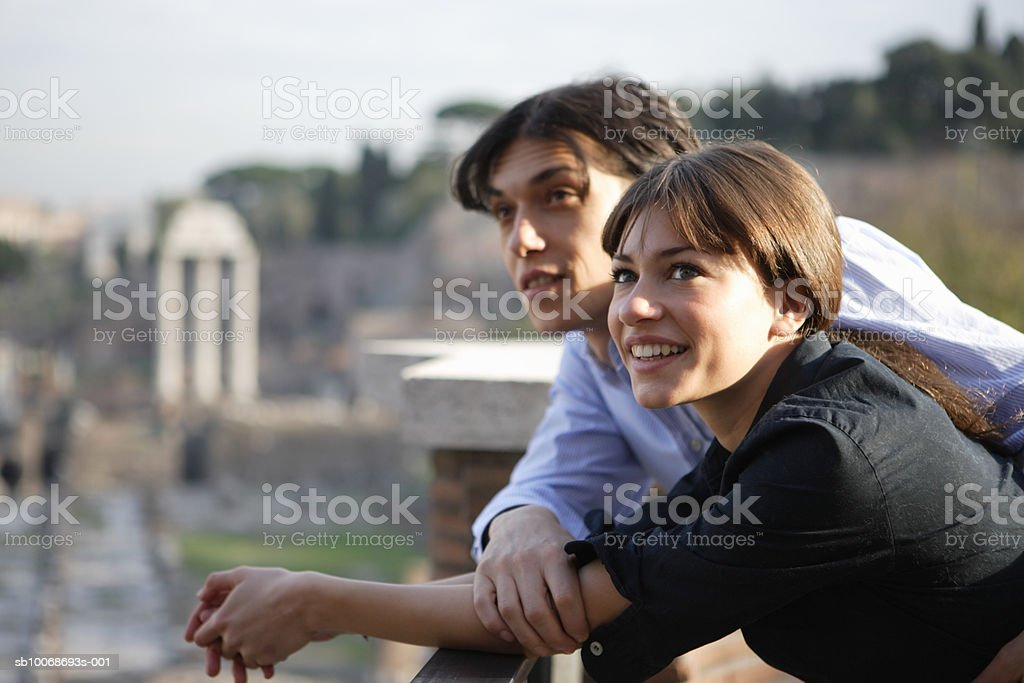 Italy, Rome, couple lining on balustrade looking at view Lizenzfreies stock-foto