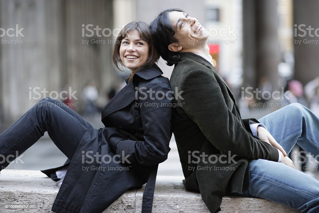 Italy, Rome, couple relaxing on wall back to back foto de stock libre de derechos