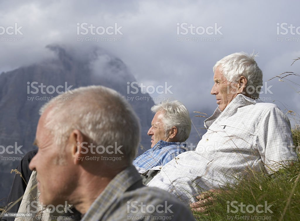 Italy, Tyrol, three senior hikers resting on grass in mountains, side view royalty-free stock photo