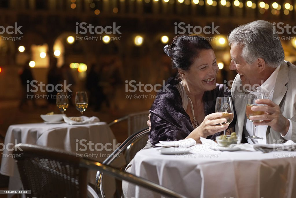 Italy, Venice, couple at restaurant table at night, outdoors stock photo