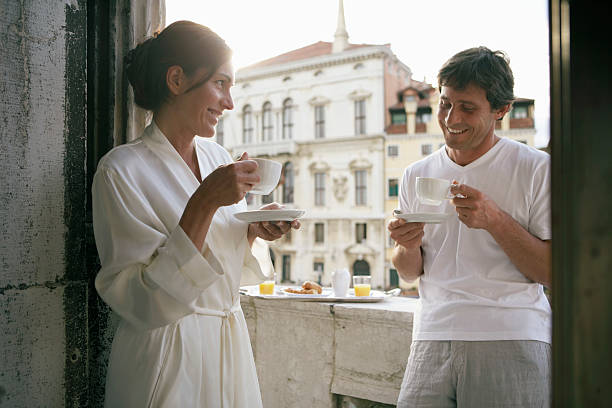 Italy, Venice, couple having  coffee on balcony, smiling stock photo