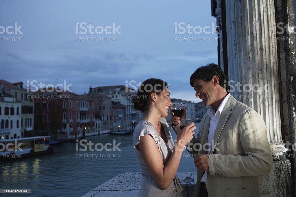 Italy, Venice, couple having drinks on balcony, smiling, dusk stock photo