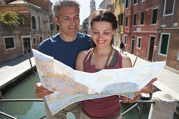 Italy, Venice, couple reading map by canal, smiling stock photo