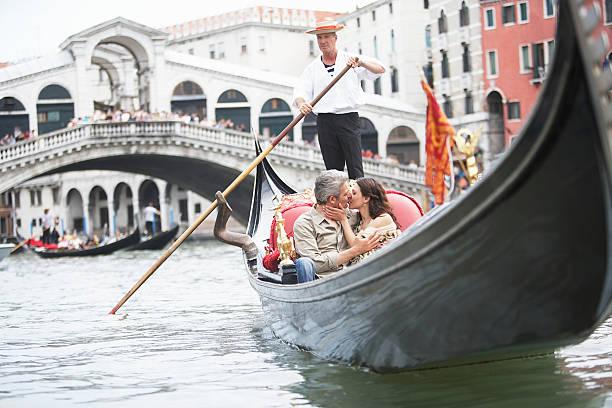 italia, venecia, par montar, besando a la góndola - venecia fotografías e imágenes de stock