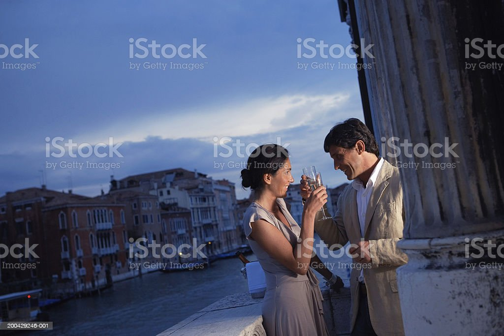 Italy, Venice, couple toasting drinks on balcony, smiling, dusk stock photo