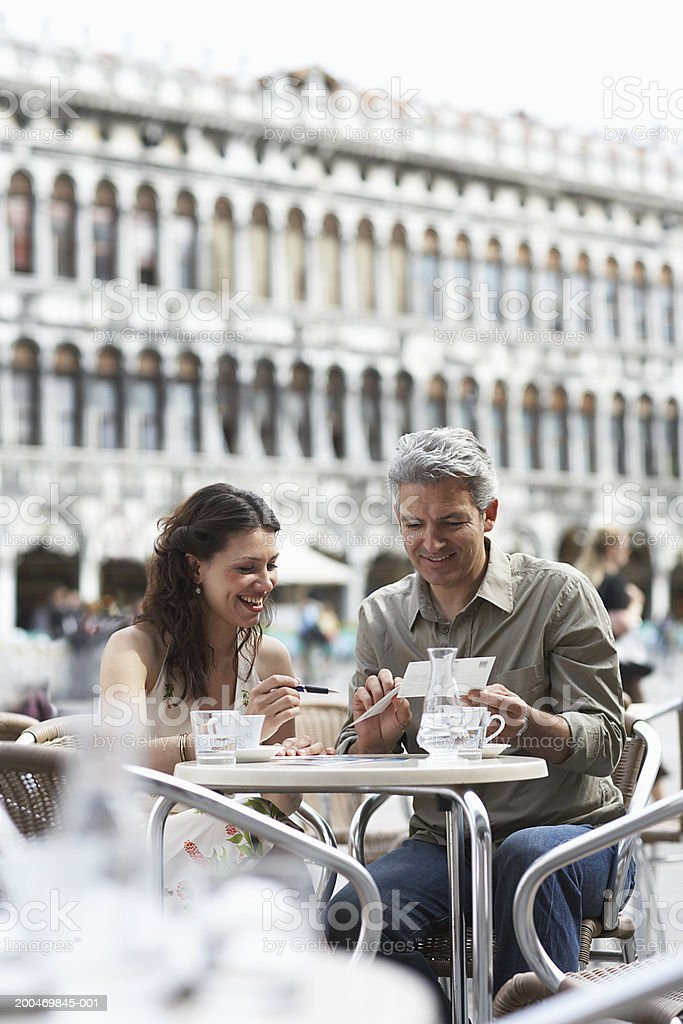 Italy, Venice, couple writing postcards at cafe table, outdoors royalty-free stock photo