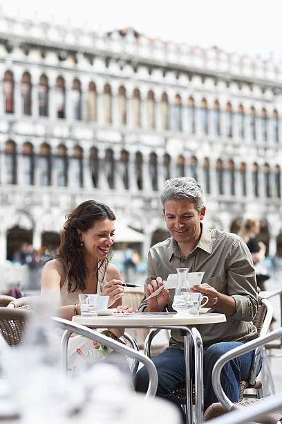 Italy, Venice, couple writing postcards at cafe table, outdoors stock photo