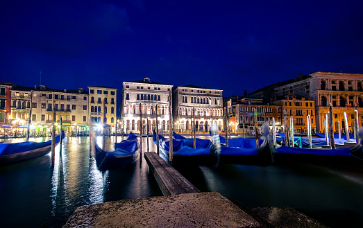 Italy Venice grand canal gondola pier row anchored overnight blurred illuminated at poles from sea water along ancient palaces
