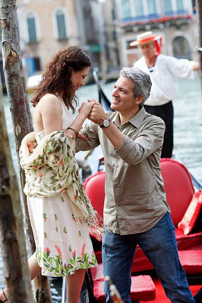 Italy, Venice, man helping woman climb into gondola stock photo