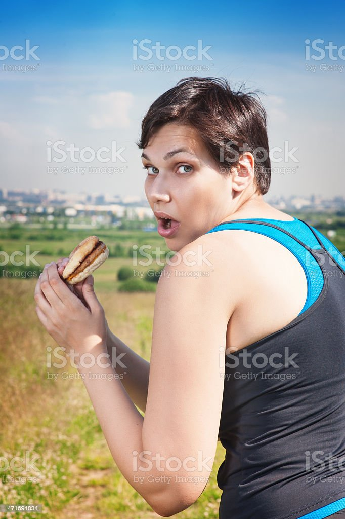 itness beautiful plus size woman stealthily eating junk food stock photo