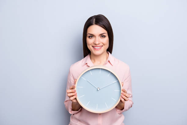 It's 10:10 o'clock. Portrait of charming pretty positive cheerful woman having round clock in hands looking at camera isolated on grey background It's 10:10 o'clock. Portrait of charming pretty positive cheerful woman having round clock in hands looking at camera isolated on grey background information sign stock pictures, royalty-free photos & images