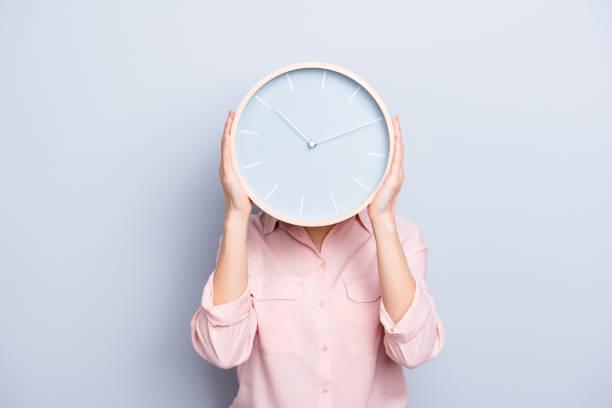 jest godzina 10:10. portret uroczej całkiem pozytywnej wesołej kobiety zamykającej zakrywającą twarz głowy z okrągłym zegarem odizolowanym na szarym tle - czas zdjęcia i obrazy z banku zdjęć