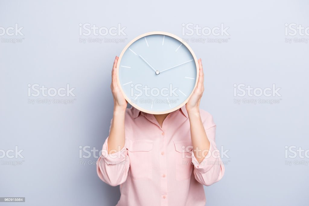 It's 10:10 o'clock. Portrait of charming pretty positive cheerful woman closing covering head face with round clock isolated on grey background stock photo