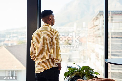 Shot of a young businessman looking thoughtfully out of a window in a modern office