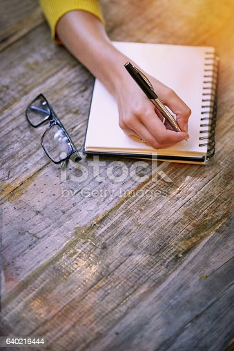 Cropped shot of a woman sitting at a table and writing in her notepad