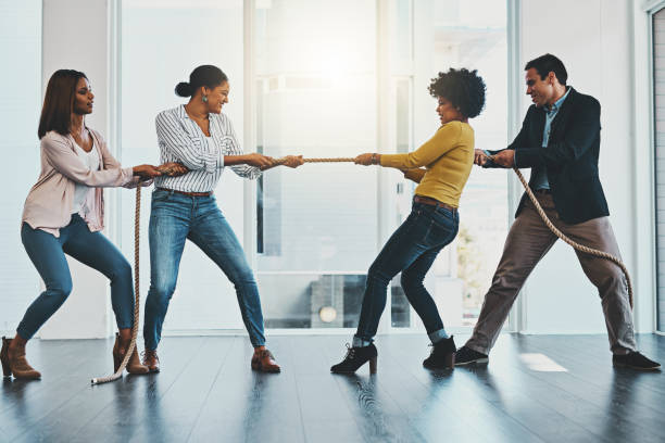 It's a competitive market out there with many challenges Shot of a group of businesspeople pulling on a rope during tug of war in an office pulling stock pictures, royalty-free photos & images