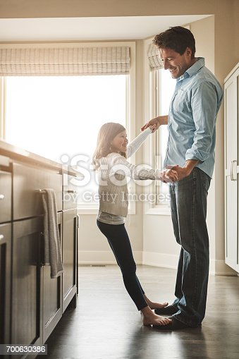 Shot of a happy father dancing with his little girl in the kitchen at home