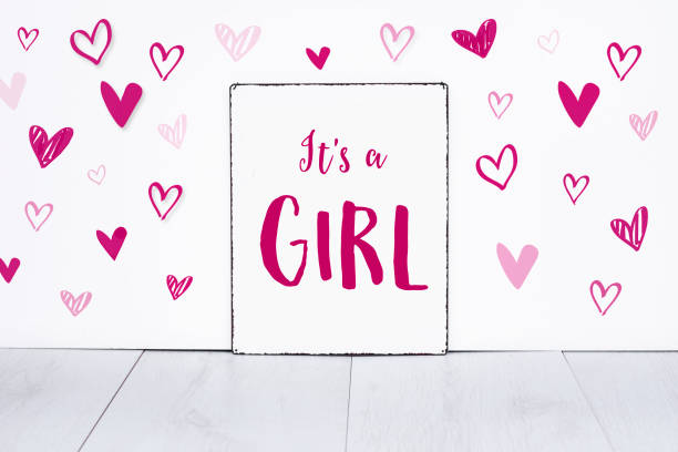 It's a girl new born baby text on sign board with cute little pink hearts on white background stock photo