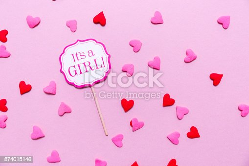 591421282 istock photo It's a girl sign at the baby shower party.  Pink solid background.  Baby shower celebration concept 874015146