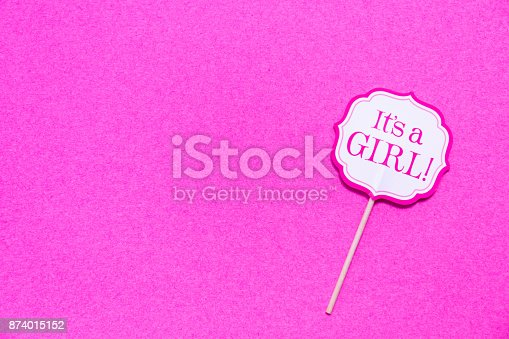 591421282 istock photo It's a girl sign at the baby shower party.  Pink solid background.  Baby shower celebration concept 874015152