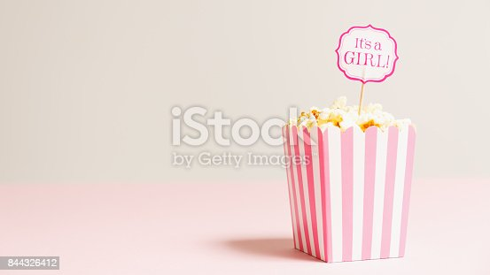 591421282 istock photo It's a girl sign in a popcorn bag at the baby shower party.  Empty background.  Baby shower celebration concept 844326412