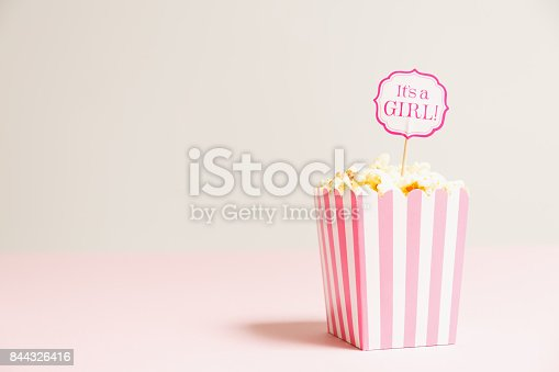 591421282 istock photo It's a girl sign in a popcorn bag at the baby shower party.  Empty background.  Baby shower celebration concept 844326416
