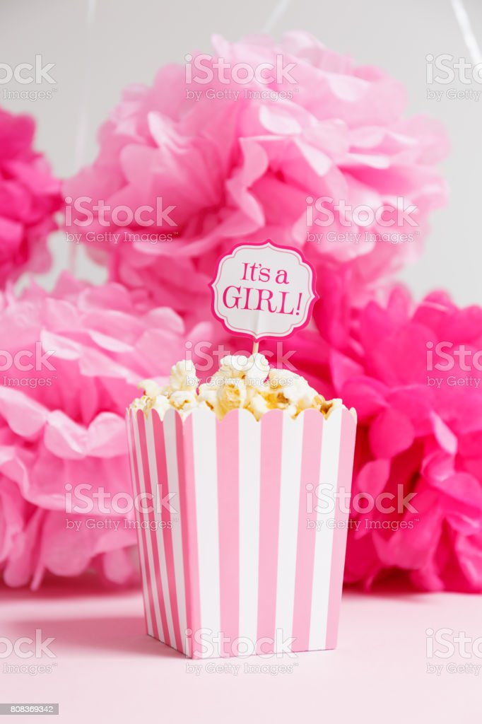 It's a girl sign in a popcorn bag at the baby shower party.  Paper flowers background.  Baby shower celebration concept stock photo