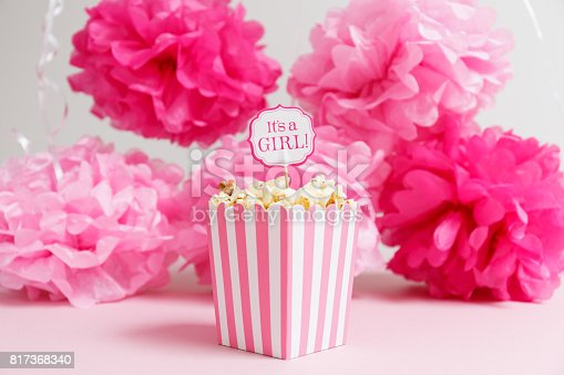 591421282 istock photo It's a girl sign in a popcorn bag at the baby shower party.  Paper flowers background.  Baby shower celebration concept 817368340