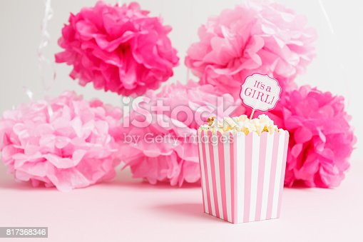 istock It's a girl sign in a popcorn bag at the baby shower party.  Paper flowers background.  Baby shower celebration concept 817368346