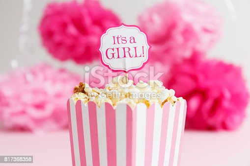 591421282 istock photo It's a girl sign in a popcorn bag at the baby shower party.  Paper flowers background.  Baby shower celebration concept 817368358