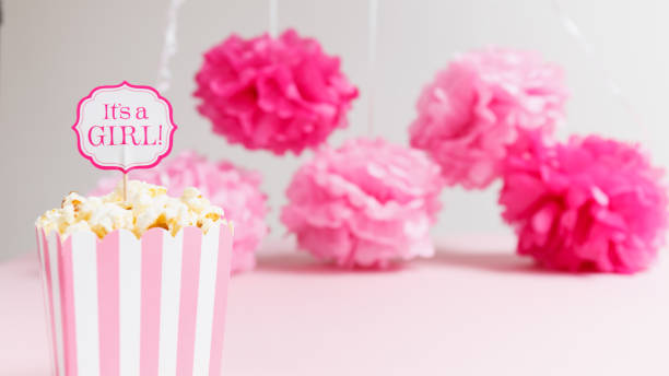 it's a girl sign in a popcorn bag at the baby shower party.  paper flowers background.  baby shower celebration concept - its a girl stock photos and pictures