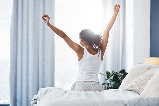 Rearview shot of an unrecognizable young woman stretching while sitting on her bed in the morning