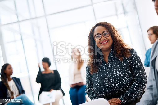 Portrait of a happy young businesswoman attending a conference