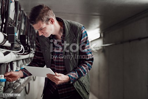 Shot of a young man using a digital tablet at a dairy farm