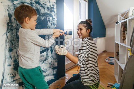 Mother and son working together on repainting a wall in their living room