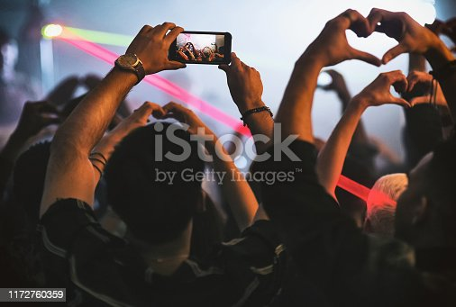 Rearview shot of a group of unrecognizable young people making the heart shape while standing in a nightclub