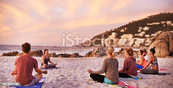 Shot of a group of people having a yoga session on the beach