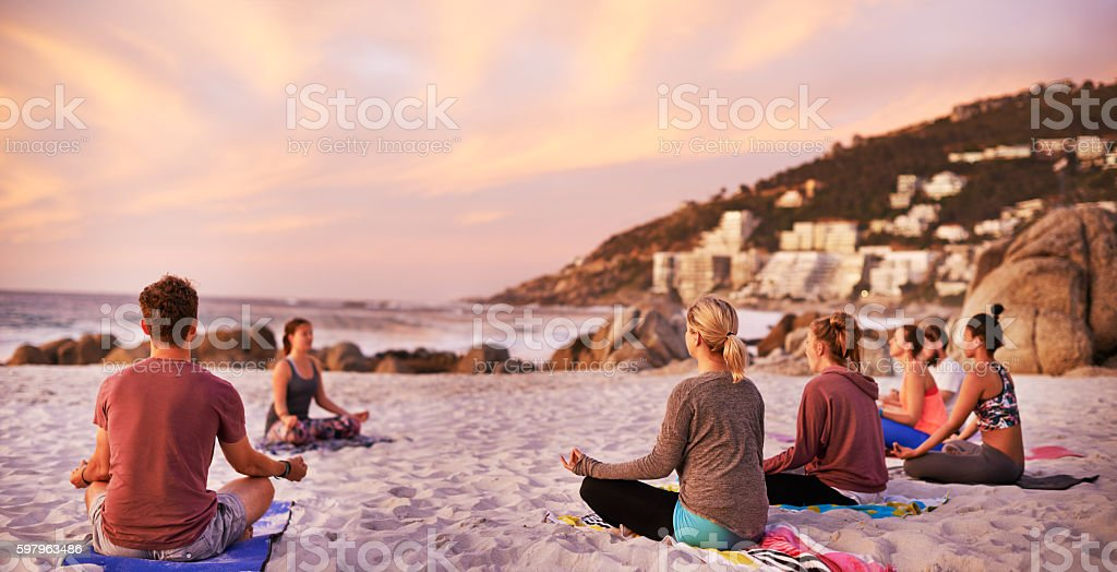 It's a perfect day for yoga at the beach stock photo