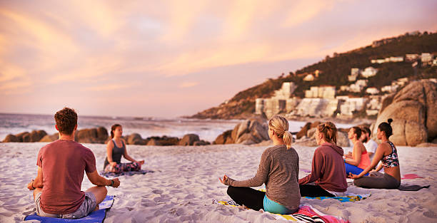 It's a perfect day for yoga at the beach Shot of a group of people having a yoga session on the beach yoga class stock pictures, royalty-free photos & images